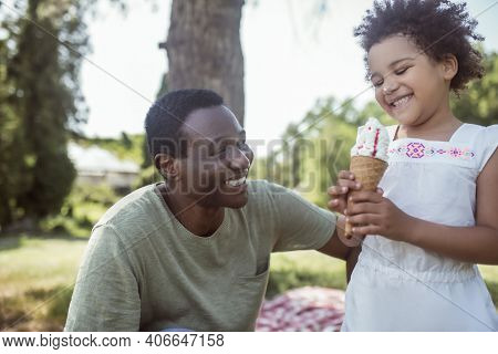 Curly-haired Cute Kid Eating Ice-cream And Spending Time With Dad