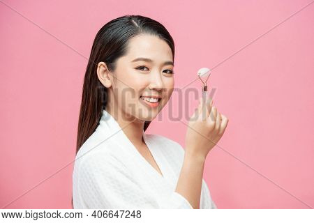 Beauty Face Care. Woman Doing Face Massage With Rose Quartz Face Roller For Spa Skin Care Treatment