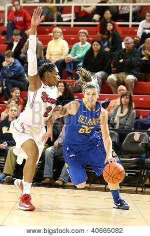 JAMAICA, NY-JAN 2: Delaware Blue Hens guard Lauren Carra (22) dribbles past St. John's Red Storm forward Amber Thompson (2) at Carnesecca Arena on January 2, 2013 in Jamaica, Queens, New York.