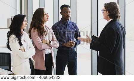 Woman Caucasian And African American Man Standing Listening To The Manager Of The Business At The Me