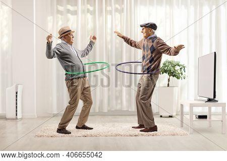 Funny elderly men spinning hula hoops inside a room