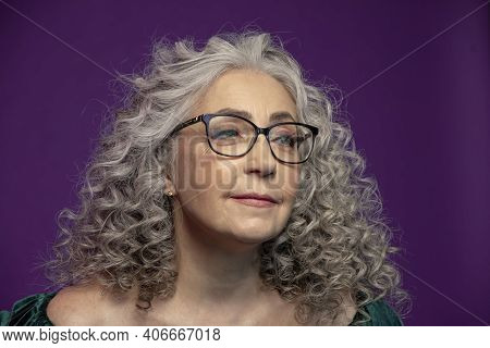 Studio Portrait Of A Smiling Elderly Woman 60-65 Years Old With Glasses, With Gray Curly Long Hair,