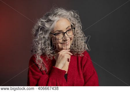 Studio Portrait Of An Elderly Woman 60-65 Years Old In A Red Sweater And Glasses, Gray Curly Long Ha
