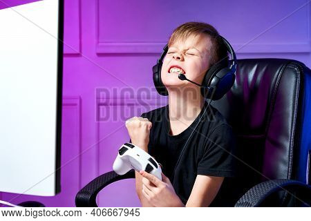 Child In A Black T-shirt With Earpieces On His Head Sits In A Computer Chair, Holds A Game Joystick,