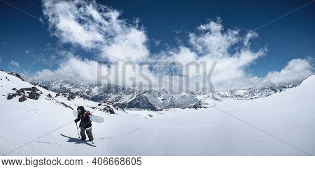 Woman Snowboarder Freerider Climb Up The Fresh Snow Riding Backcountry. Peaks Of Mountains And Blue