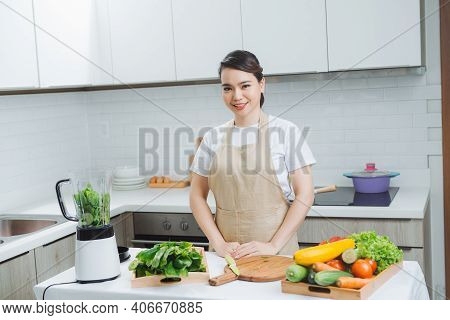 Woman Cooking Healthy Detox Smoothie With Fresh Fruits And Green Spinach, Salad Leaves. Lifestyle De