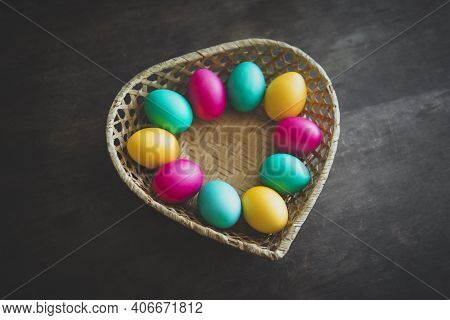 Easter Eggs In Basket On Rustic Wooden Background. A Basket Made Of Straw In The Form Of A Heart Wit