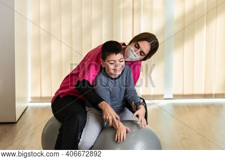 Disabled Child And Physiotherapist On Top Of A Peanut Gym Ball Doing Balance Exercises. Pandemic Mas