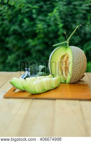Closeup To Juicy Fresh Green Melon On Wood Plate