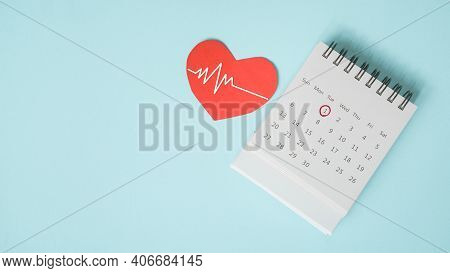 Red Heart With Heartbeat And White Calendar Page With Circle Marked On 1st Date On Grunge Blue Backg