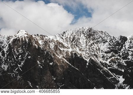 Atmospheric Minimalist Alpine Landscape With Snowy Rocky Mountain Peak. Low Clouds Above Massive Sno
