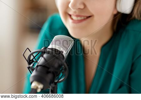 technology, mass media and people concept - close up of woman with microphone and headphones talking and recording podcast at studio