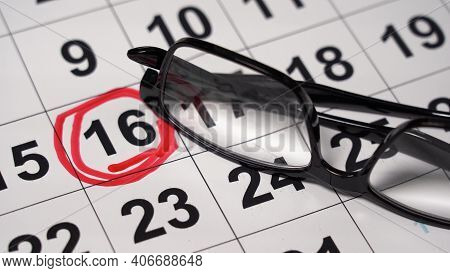 The Date Is Highlighted In Red On The Calendar. Glasses Lie On A Calendar Sheet With A Highlighted D
