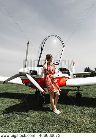A Lovely Girl In A Beautiful Dress Stands Near A Private Plane. Light Plane Near The Hangar. Girl Is