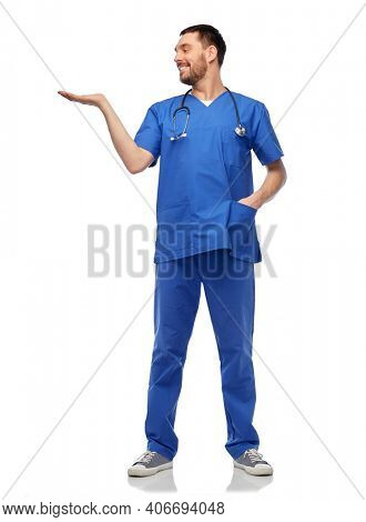 healthcare, profession and medicine concept - happy smiling doctor or male nurse in blue uniform with stethoscope holding something imaginary on empty hand over white background
