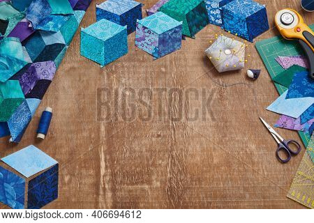 Fragment Of Tumbling Blocks Quilt, Accessories For Quilting On A Wooden Surface. Space For Text.