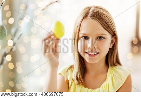 easter, holidays and people concept - happy girl decorating willow branches with toy eggs at home over bokeh lighs