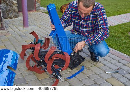 Man Assembles A Cultivator Of The Walk-behind Tractor, Work On Assembling A Cultivator Of The Walk-b
