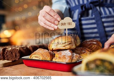 Sales Assistant In Bakery Putting Dairy Free Label Into Stack Of Freshly Baked Baked Cinnamon Buns