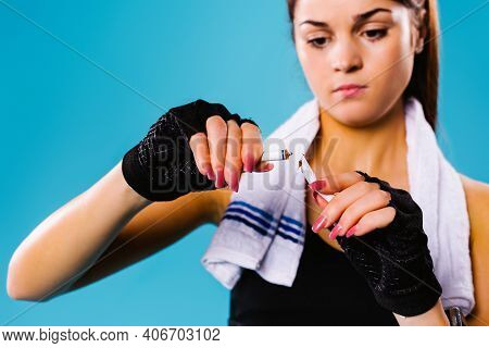 Enlarged Photo Of A Sports Girl Breaking A Cigarette On A Blue Background. Gives Preference To A Hea
