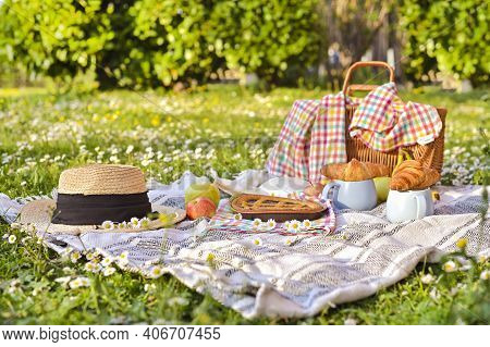 Picnic Basket On A Plaid And A Green Meadow With Flowers. Lunch Sweet Cake, Croissants, Drinks, Frui