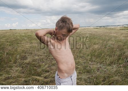 Boy In Shorts Stands In The Field. Boy Looks To The Sky. Dreamer Guy