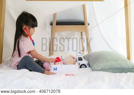 Asian Cute Little Girl Playing Doctor Role Model While Sitting In A Blanket Fort In Living Room At H