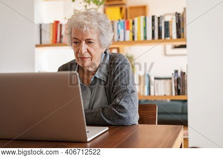 Concentrated senior woman browsing internet on laptop at home. Elderly retired lady using computer and smiling in living room. Old casual lady typing on computer keyboard and surfing the net.