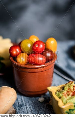 closeup of some cherry tomatoes and some baby plum tomatoes of different colors in an earthenware bowl, on a gray rustic wooden table, next to a yellow ceramic bowl with some guacamole