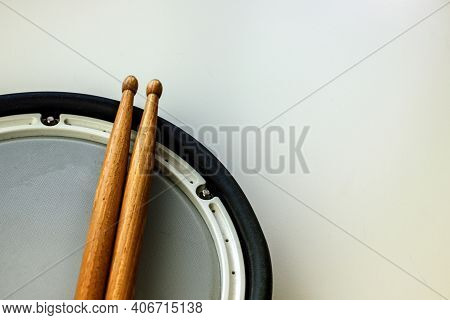 Drum Sticks Made Of Wood And A Pad From An Electronic Drum Kit Close-up. Music Hobby Concept. Home A