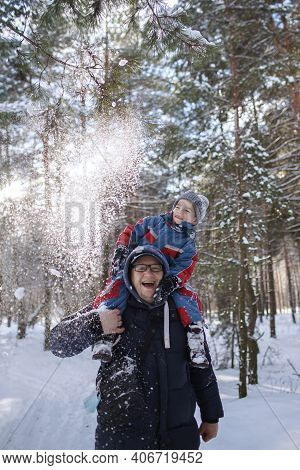 Happy Son On The Shoulders Of His Father Shaking Off Snow From A Branch And Enjoying Winter Season.