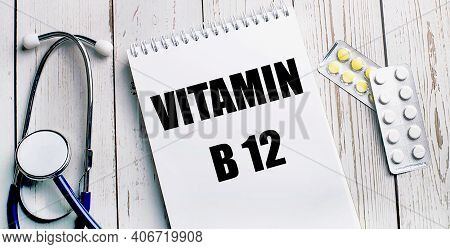 On A Light Wooden Table Lie A Stethoscope, Pills And A Notebook With The Inscription Vitamin B12. Me