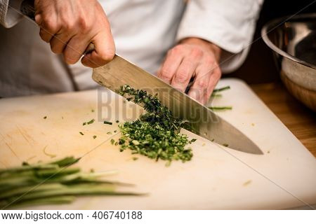 Close-up Of Hands Of Chef Chopping Green Onion With Knife On Cutting Board