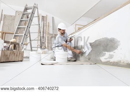 Man Plasterer Construction Worker At Work, Takes Plaster From Bucket And Puts It On Trowel To Plaste
