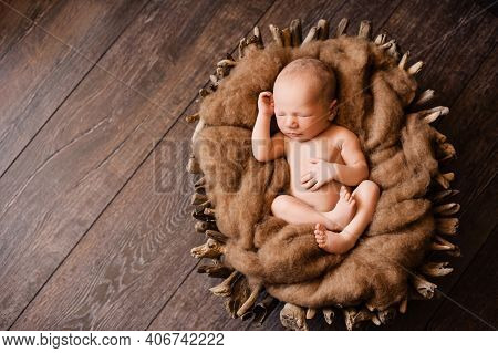 2. Newborn Sleeping On His Back In A Brown Basket At A Newborn Photoshoot