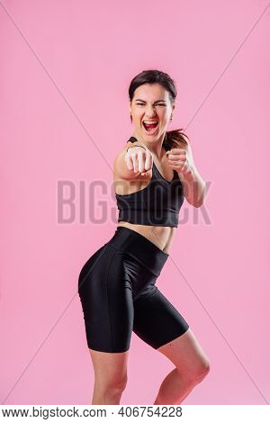 Slim Sportswoman Kicking The Air, With Hand And Leg Up. Athletic Girl Doing Boxing Exercises, Making