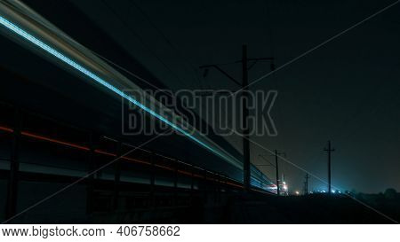 A Train Shot In Motion At Night. The Train Moves On The Railroad Into The Distance. Blurred Train.