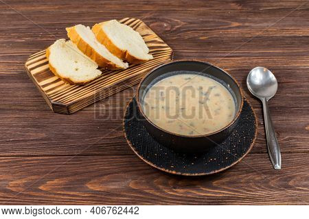 A Bowl Of Homemade Mushroom Puree Soup With Herbs And Bread On A Wooden Table. Homemade Vegetarian M