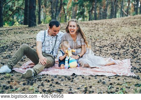 Happy Family, Wearing Light Clothes, Sitting In A Pine Forest. Mom Handing Her Son A Soft Toy Of A G