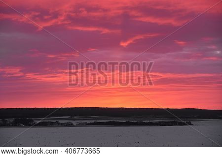 Natural Sunset Sunrise Over Field Or Meadow. Pink Color Sky Over Winter Snowy Ground. Landscape Unde