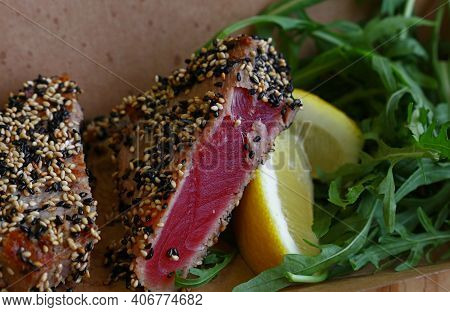 Close Up Street Food Brown Carton Box Portion Of Lightly Seared Tuna Steak With Sesame Seeds And Aru