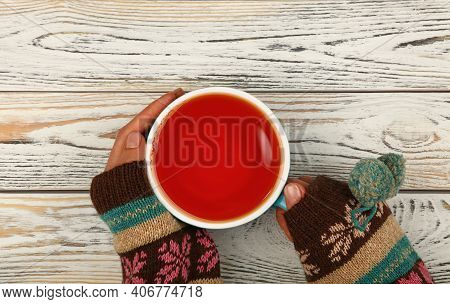 Close Up Two Woman Hands Hold And Hug Big Full Cup Of Black Tea Or Red Fruit Over White Wooden Table