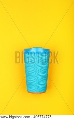 Close Up One Crimped Disposable Pastel Blue Paper Takeaway Coffee Cup Over Vivid Yellow Background,