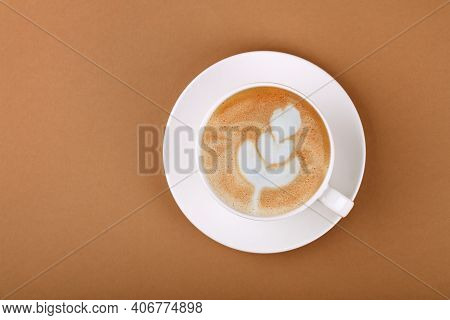 Close Up One Cup Full Of Cappuccino Coffee On White Saucer Over Brown Paper, Elevated Top View, Dire