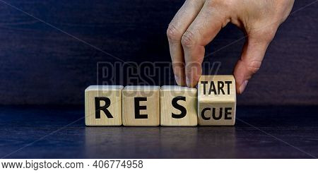 Rescue And Restart Symbol. Businessman Hand Turns Cubes And Changes The Word 'rescue' To 'restart'.