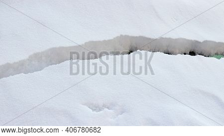 Wide Crack On The Surface Of Fluffy White Snow. Danger Of Avalanche.