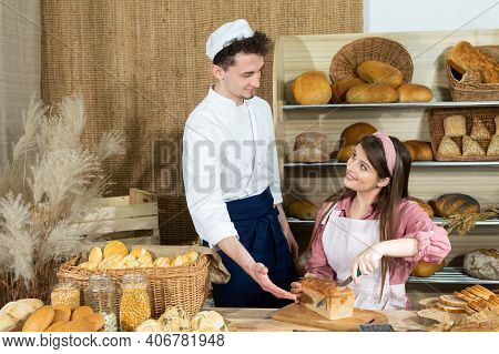 A New Clerk Learns To Cut The Bread Properly Under The Bakers Supervision. An Attractive Saleswoman