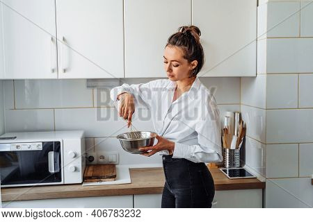 Beautiful, Attractive, Smiling Young Woman Kneading Dough With Whisk For Banana Pancakes In Steel Di