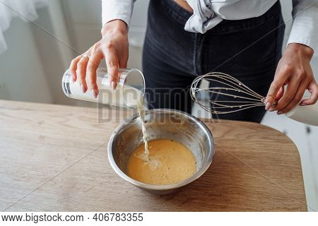 Diy Home Cooking Concept. A Bright Brunette Woman Sifting The Flour For Pancakes Through A Sieve, Sa