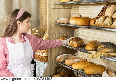 An Attractive Saleswoman From A Bakery Shop Reaches For The Bread From The Shelf. A Young Girl As A
